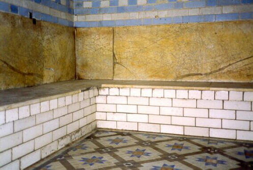 A corner of the hot room with marble seats and tiled floor
